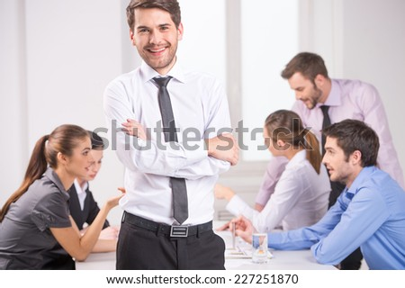 Business meeting - manager discussing work with his colleagues. man standing on foreground with crossed hands and team on background - stock photo