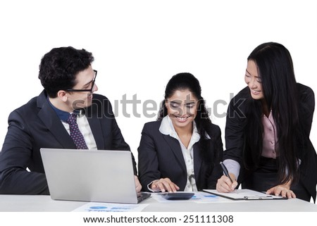 Business meeting of multiracial entrepreneurs with laptop, calculator, and documents - stock photo