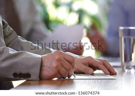 Business meeting or lecture with businessman writing or signing contract - stock photo