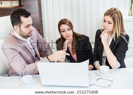 Business meeting, showing contract document, casual conversation at office, one man two beautiful females. - stock photo