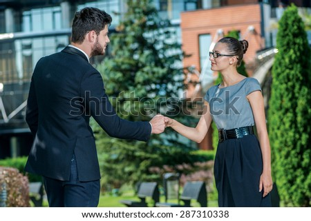 Business meeting. Smiling businessman and successful businesswoman in formal clothes standing on the street and shake hands with each other. Young businesspeople smiling at each other - stock photo