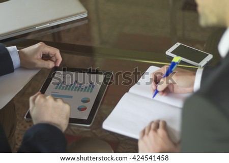 Business meeting. Tablet displaying column graph, stacked bar graph and pie graph on the screen and two young men discussing information while one of them takes notes. All screen graphics are made up. - stock photo
