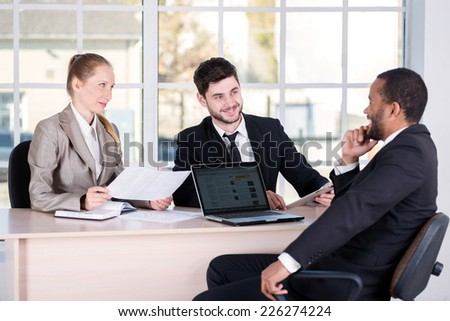 Business meeting. Three successful business people sitting in the office and do business while businessmen communicate with each other and work at a laptop - stock photo