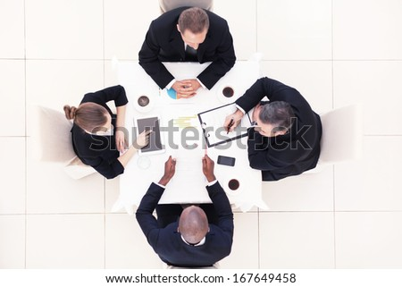 Business meeting. Top view of four business people in formalwear sitting at the table and discussing something - stock photo