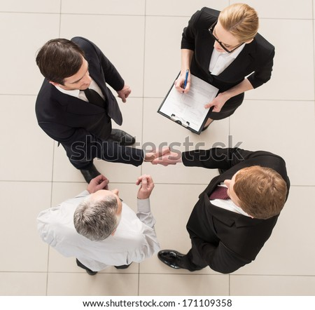 Business meeting. Top view of four people in formalwear standing close to each other while two of them handshaking - stock photo