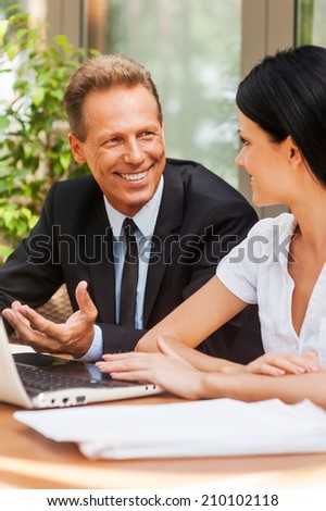 Business meeting. Two business people in formalwear discussing something and smiling while both sitting at the table outdoors