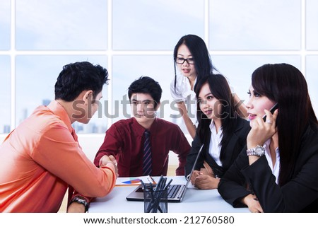 Business meeting with team showing agreement between two people at office - stock photo
