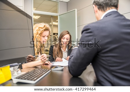 Business meeting, woman signing a contract in a lawyer office - stock photo