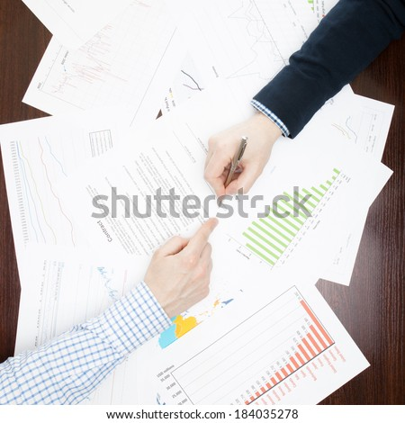 Business men analyzing some business information at the desk - view from the top - 1 to 1 ratio - stock photo
