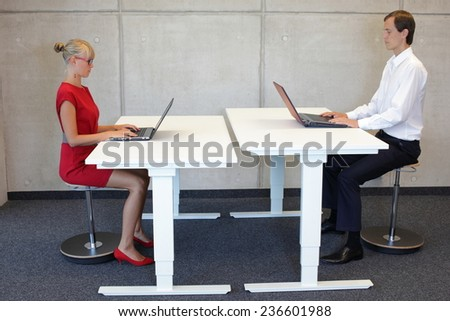 Business men and women working in correct sitting posture with laptops on pneumatic leaning seats  at electric  height adjustable desks in office - stock photo