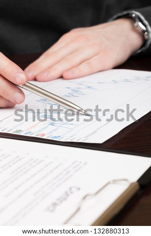 Business men reading contract with pen in hand