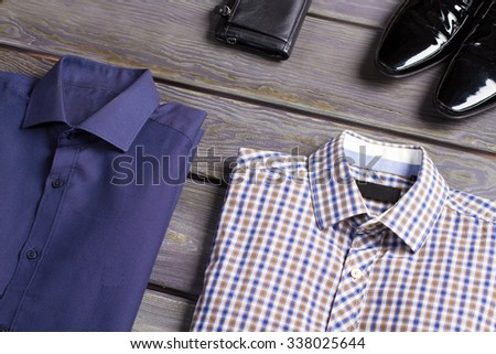 Business men's shirts, shoes and purse. Men's things on a wooden background. - stock photo