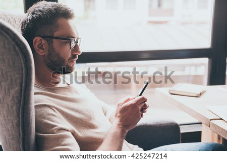 Business message. Side view of handsome man using his smartphone while sitting in chair in front of window - stock photo