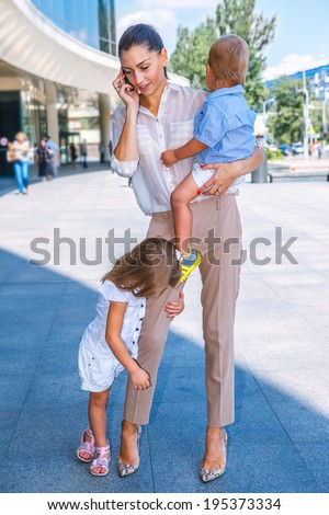 Business mother speaking over the cellphone, with two kids - stock photo