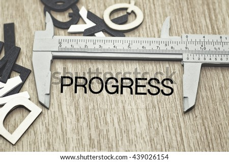 Business motivation and finance concept, vernier caliper with word PROGRESS over wooden floor and alphabetical word made from wood background - stock photo