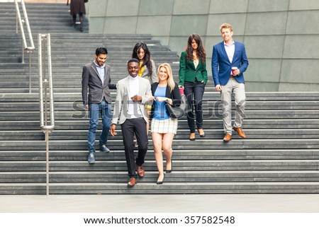 Business multiracial group walking down a staircase in London. They all are young, smiling and wearing smart casual clothes. Mixed race group. Teamwork and business concepts.