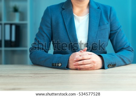 Business negotiation skills with female executive sitting at office desk with confident pose and hands crossed, body language for determination and willpower