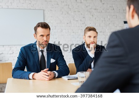 Business negotiations - three businessmen discussing during business meeting - stock photo