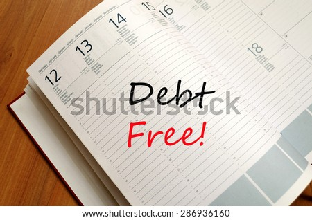 Business Notepad on wooden table Debt Free concept - stock photo