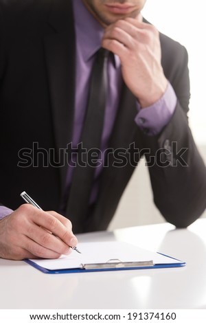 Business notes. Close-up of a businessman's hand with a gilded pen writing something.