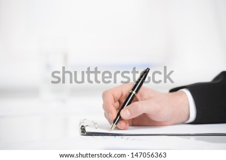 Business notes. Close-up of hand writing something in a note pad