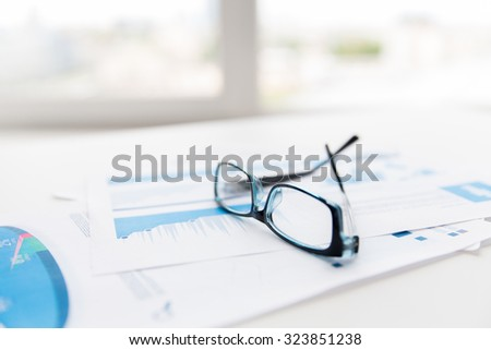 business, objects and statistics concept - close up of eyeglasses and files on office table - stock photo