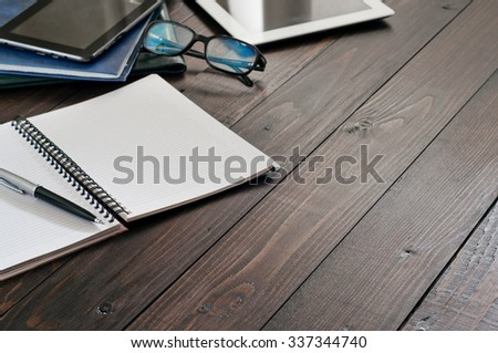 Business Objects (tablet computer, glasses for computer, notebook, leather folders, pen). Open notebook with blank pages on wooden office desk close up. Top view. Free space for text. Copy space - stock photo