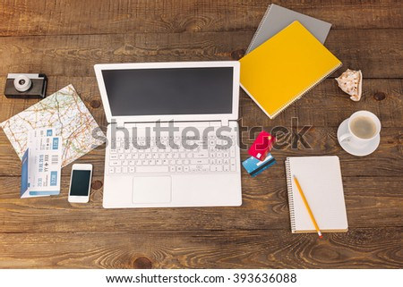 Business objects. Top view creative photo of objects on vintage brown wooden table. There are map, tickets, credit cards, notebook, coffee, laptop and mobile phone on it with space for your logo
