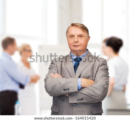 business, office and education concept - serious buisnessman or teacher in suit with team on the back - stock photo