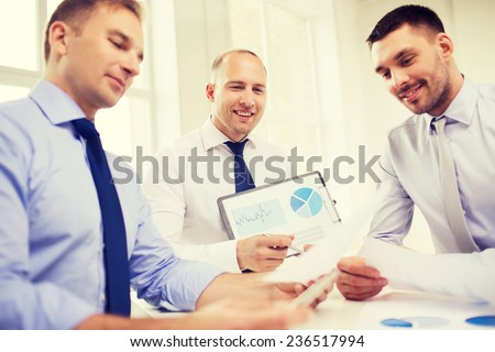 business, office and people concept - smiling businessmen with papers in office - stock photo