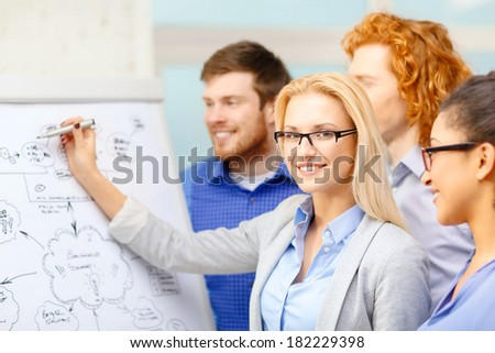business, office and startup concept - smiling smiling businesswoman in eyeglasses with team team on the back