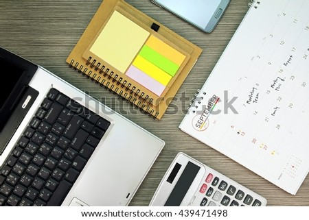 Business office desk with working schedule. Well organized working space with office supplies and eco-friendly stationaries. (Color Processed)