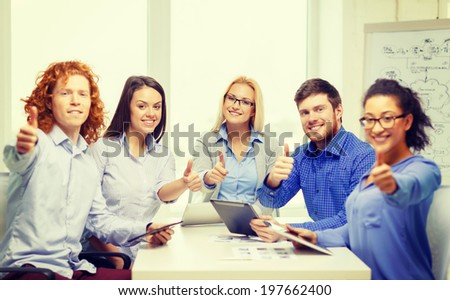 business, office, gesture and startup concep - smiling creative team with table pc computers and papers showing thumbs up in office