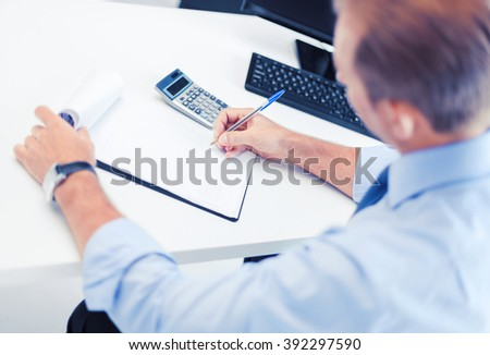business, office, school and education concept - businessman with notebook and calculator - stock photo