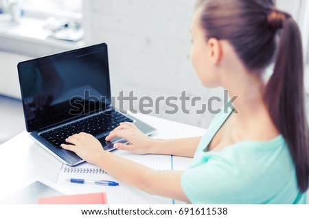 business, office, school and education concept - businesswoman working on laptop with blank screen