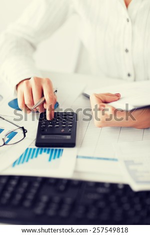 business, office, school and education concept - woman hand with calculator and papers - stock photo