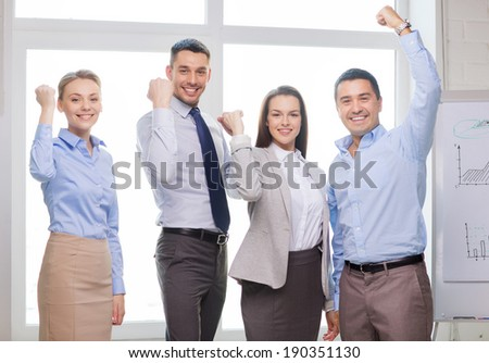 business, office, success and victory concept - happy business team celebrating victory in office - stock photo