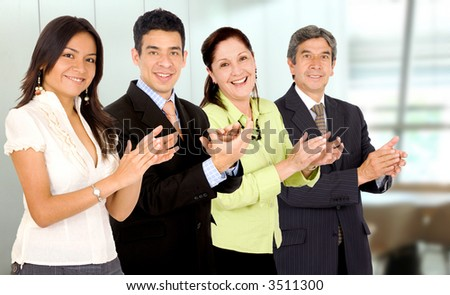 business office team smiling and applauding while facing the camera - stock photo