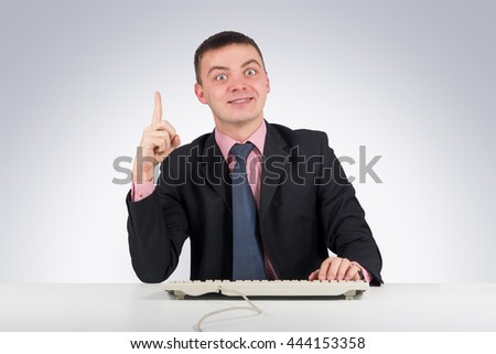 Business,office, technology, finances and internet concept - Businessman at office holding finger up: idea or warning on gray background - stock photo