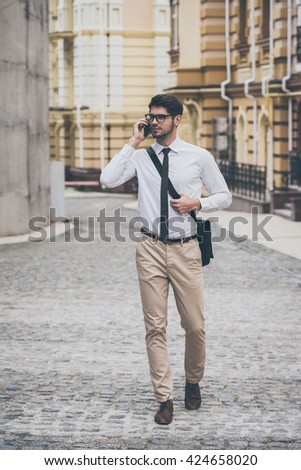 Business on a go. Confident young man in glasses talking on mobile phone while walking outdoors - stock photo