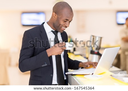 Business on the go. Cheerful young African man in formalwear using his laptop while standing at the bar  - stock photo