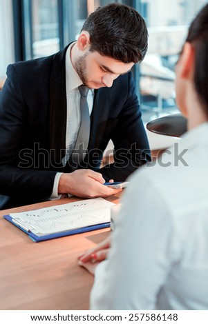 Business on the go. Handsome young man messaging on his mobile phone while having business lunch his female colleague at the restaurant