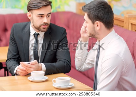 Business on the go. Two handsome businessmen drinking coffee and communicating to each other while having lunch break in the cafe - stock photo