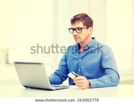 business, online banking, internet shopping concept - smiling man with laptop and credit card at home - stock photo
