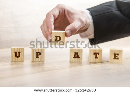 Business or education concept of updating a system, offer or personal knowledge and abilities  - male hand arranging wooden cubes with letters to read Update. - stock photo
