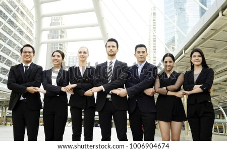 Business outdoor concept, Business team. Success business people team arms cross with shook hands together in the city outdoors. International business team over modern urban background.