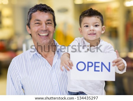 Business owner and son holding an open sign