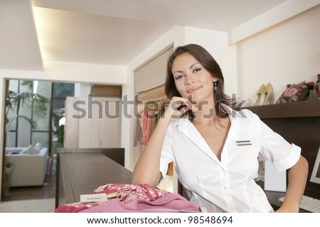 Business owner leaning on her store's payment area, feeling proud. - stock photo