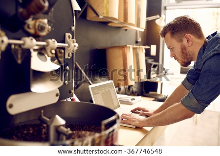 Business owner of a coffee roastery checking his laptop - stock photo