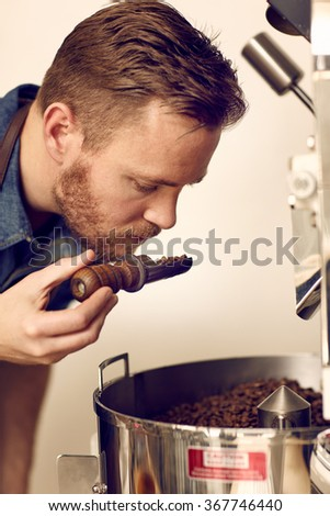 Business owner smelling freshly roasted coffee beans for aromati - stock photo